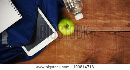 Schoolbag with apple and digital tablet on wooden table