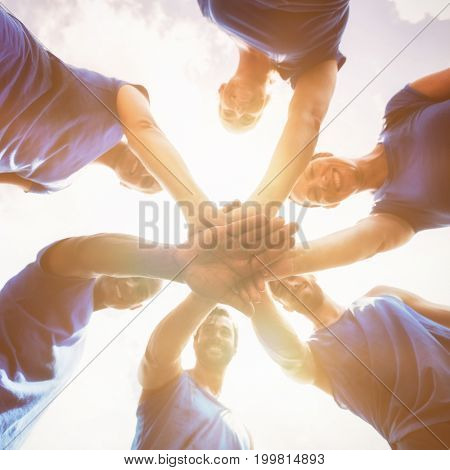 Fit people with hands stacked against sky at camp