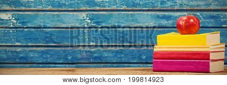 Stacked books with apple on wooden table