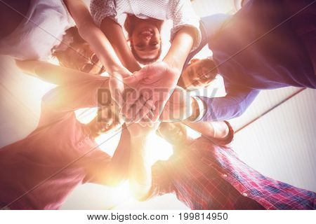 Business people forming hands stack at office