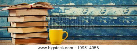 Stack of books with coffee cup on wooden table
