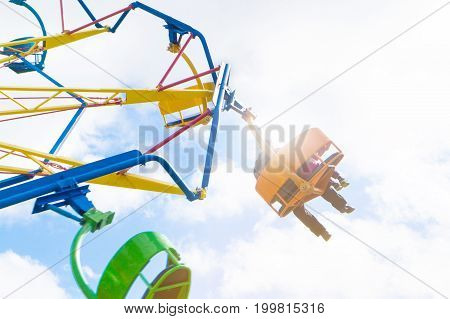 People in amusement park ride. Adult man and with kid in theme park having fun.