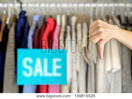 Unhappy and dissatisfied customer giving thumbs down in a clothing store for bad service or product quality. Disappointed shopper in fashion clothes store showing negative hand gesture.