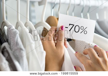 Female customer browsing clothes in a shop. Woman shopping for fashion offer and deal. Holding price tag with minus seventy percent or 70% sale, bargain and reduced cheap prices in clothing store.