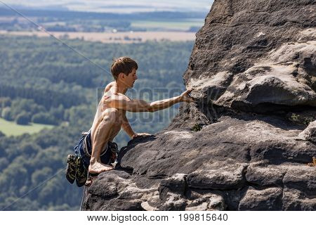 Lilienstein Germany - August 14 2017. A young climber with a muscular body climbs barefoot along the edge of a sandstone rock. Climber in Saxon Switzerland Lilienstein rock Germany.