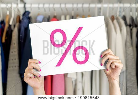 Sale, bargain and reduced cheap prices in clothes store or shop. Special fashion offer and deal. Woman holding advertising and marketing banner with % and percent symbol and icon with both hands.