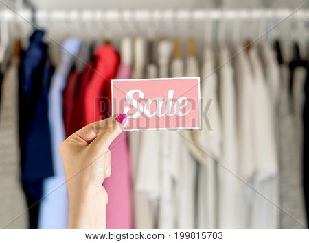 Sale in clothing shop. Woman holding discount coupon.