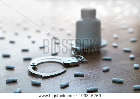 Drug addiction, medical abuse and narcotics hook and dependence concept. Medicine bottle handcuffed and surrounded by many pills. Tablet overdose. Withdrawal symptoms, depression and problem.