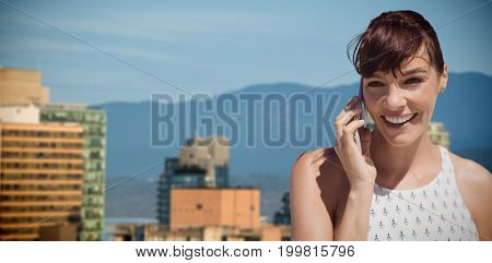 Businesswoman using cell phone against buildings in city against blue sky