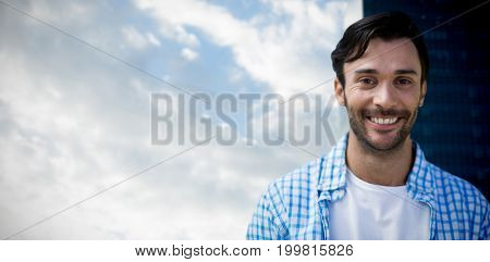 Portrait of handsome man against cloudscape in sky by glass building