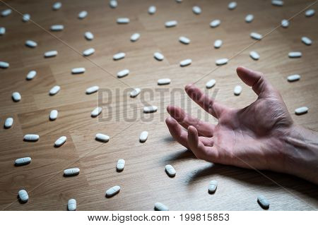 Drug addiction, medical abuse and narcotics hook and dependence concept. Drug addict with withdrawal symptoms lying on floor. Tablet overdose. Depression and problem. Hand surrounded by many pills. poster