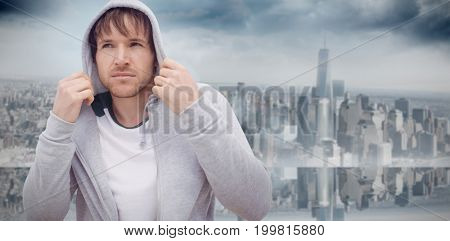 Portrait confident, cool young Latino man wearing hoody against room with large window looking on city