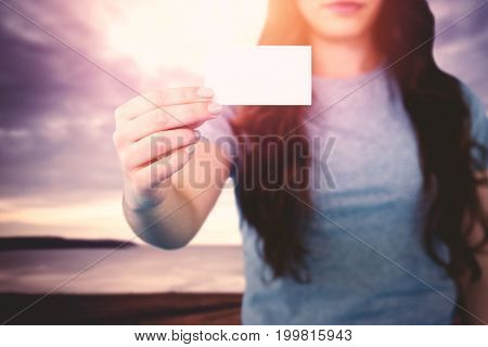 Woman holding blank card against grey sky over ocean