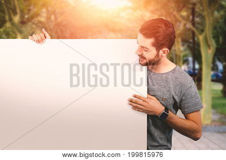 Smiling young man holding placard against white background against footpath amisdt treelined