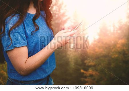 Women touching her phone  against autumn trees in forest