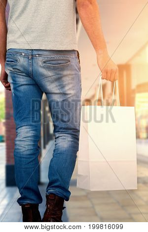 Composite image of low section of man carrying shopping bag
