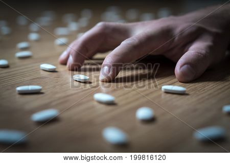 Drug addict with withdrawal symptoms lying on floor. Drug addiction, medical abuse and narcotics hook and dependence concept. Tablet overdose. Depression and problem. Hand surrounded by many pills.
