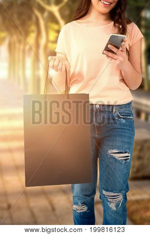 Women holding bag with blank space against sidewalk with trees
