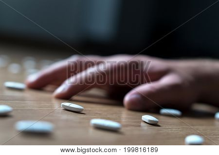 Drug addiction, medical abuse and narcotics hook and dependence concept. Drug addict with withdrawal symptoms lying on floor. Tablet overdose. Depression and problem. Hand surrounded by many pills.