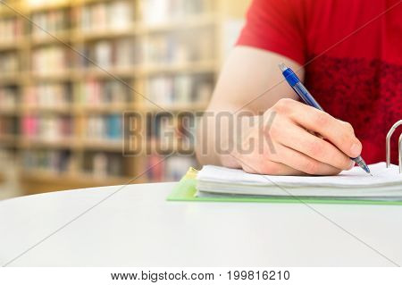 Young athletic man and student studying and writing notes in public or school library in college or university. Stack and pile of books, pen and paper on table. Negative copy space.