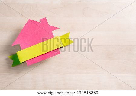 House for sale. Cottage made from cardboard paper on wooden table. House warming party template. Empty blank ribbon with negative copy space. Real estate business. Selling and buying home.