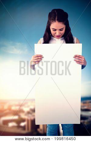 Women holding blank poster  against cityscape against blue sky