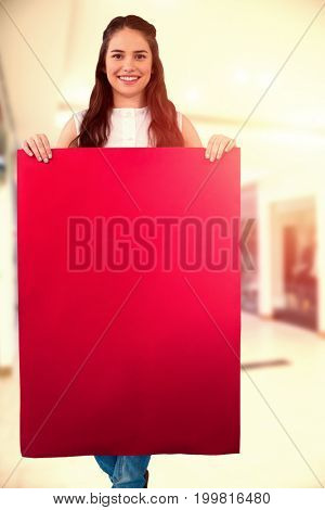 Women holding blank poster  against interior of modern shopping mall