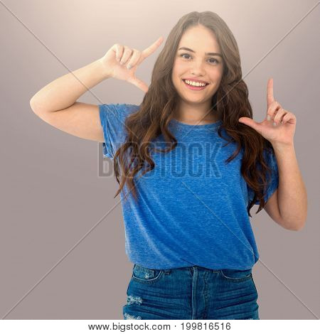 Portrait of female fashion model making frame with hands against grey background