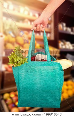 Cropped hand of man holding bag with vegetables against fruits in super market