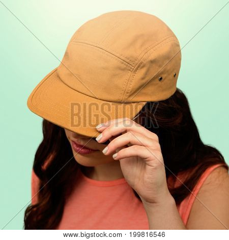 Woman with long hair wearing brown cap against blue background