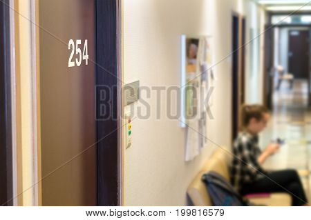 Doctor's waiting area or room in hospital. Principal's or curator's office in school. Patient or student waiting in the hallway. Door with a number.