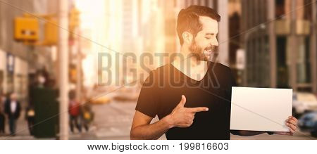 Smiling young man pointing towards blank cardboard against picture of a city