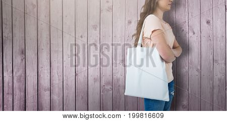 Women holding bag with blank space against digitally generated grey wooden planks