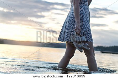 Beautiful woman in sunset walking in water and lake holding shoes in hand. Beach lifestyle view. Sad and dramatic mood.