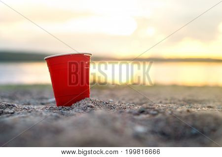 Red party cup in sand at sunset. Summer beach party concept with copy space.