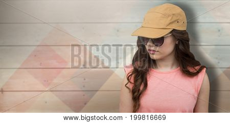 Attractive model wearing cap and sunglasses against colored wood