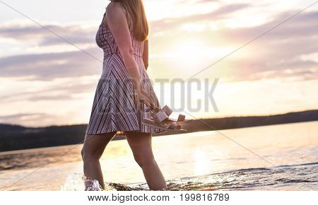 Freedom and happiness concept. Young attractive woman walking in lake water at sunset. Carefree and happy lifestyle. Holding sandals in hand. Hot summer night.