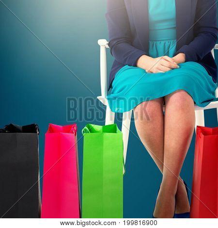 Women sitting next to bags  against dark blue background