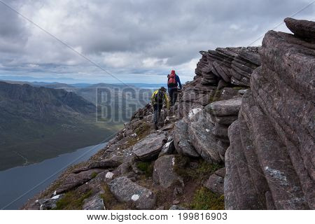 Two Walkers Travering Ridge Trail Overlooking Lake In Scottish Highlands