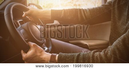 Midsection of male customer test driving in car