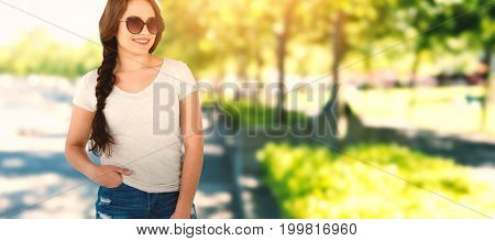 Smiling beautiful model standing with hands in pockets against blur view of park