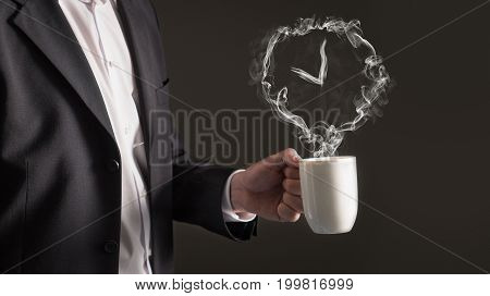 Coffee break concept. Clock sign from steam. Smoke forming a time symbol. Business man in a suit holding a hot beverage in a mug and tea cup.