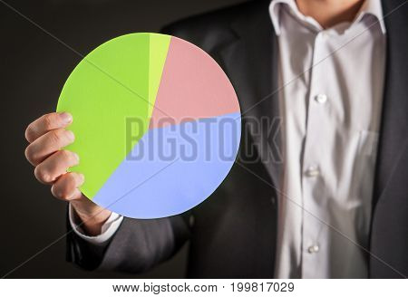 Business man holding a pie chart made from cardboard paper. Visual demonstration of finance statistics and market and sales situation.