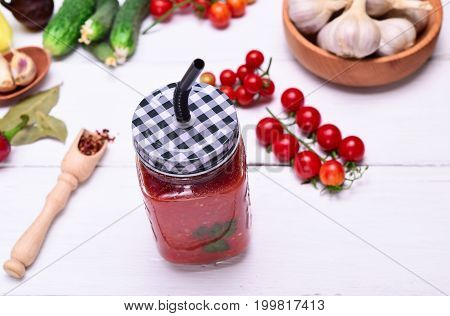 Freshly squeezed tomato juice in a glass jar with a straw on a white wooden table top view