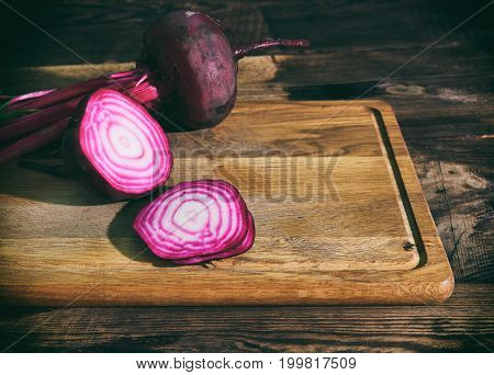 Sliced red beet on a wooden kitchen board close up