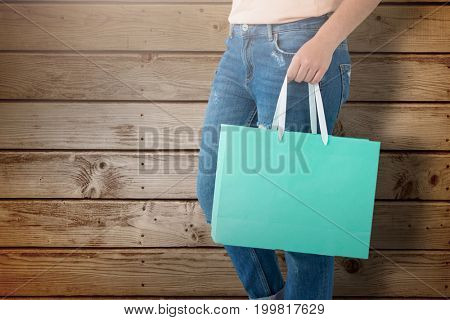 Women holding shopping bag  against wooden planks background