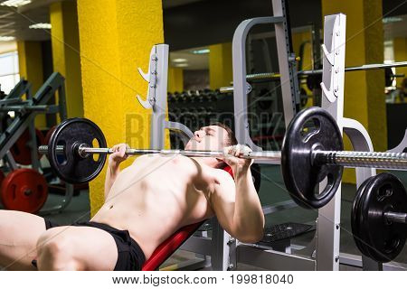 Weightlifter at the bench press lifting a barbell on an incline bench
