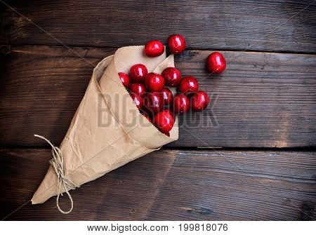 Ripe red cherry in a paper bag on a brown wooden background empty space on the right