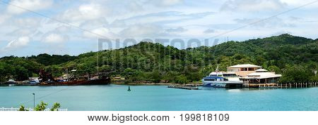 The panoramic view of Roatan Island coastline with a ferry station and a sunken ship (Honduras).