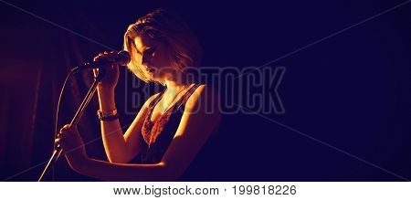 Thoughtful woman with microphone standing at nightclub